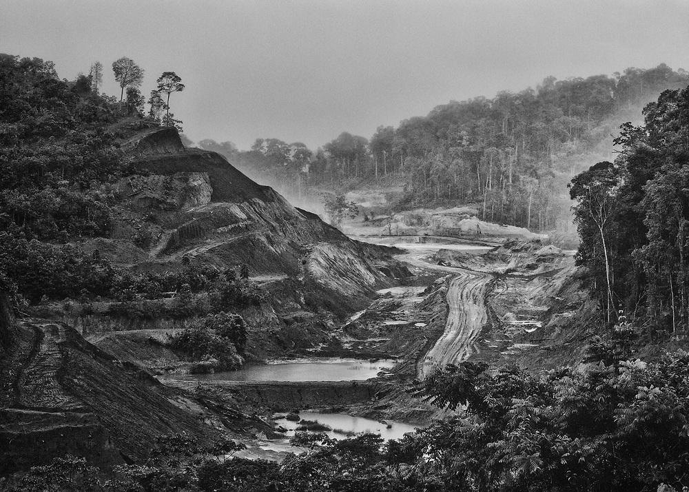 Saint-Elie, Guyane, 2015.<br /> <br /> Saint-Elie est un des plus anciens villages de l'intérieur guyanais, créé par l'orpaillage au XIXe siècle. Pratiquement déserté et très fortement enclavé, Saint-Élie a connu sa période de gloire avec la saga de l'orpaillage illégale au début des années 2000. Plusieurs centaines de clandestins Brésiliens s'y installent. Le bourg devient hors de contrôle. En 2008, l'opération Harpie menée par les Forces Armées en Guyane oblige les clandestins à quitter les lieux et 22 commerçants de Saint-Élie sont appelés à comparaître pour complicité d'orpaillage illégal. Saint-Élie devient un village fantôme avec ses 38 électeurs inscrits mais installés pour la large majorité sur le littoral guyanais. De fait une dizaine de personnes vivent aujourd'hui sur place : cinq gendarmes mobiles qui se relaient toutes les deux semaines et veillent à ce qu'aucun clandestin ne s'installe, au moins deux agents municipaux permanents, un brésilien et un unique commerçant qui attend le retour des clandestins. Si le territoire de la commune s'étend sur 5680 km2, le bourg de Saint-Elie bâti à flanc de colline et assoupi sur un gisement d'or n'est plus propriétaire de l'intégralité de son foncier. Le village est maintenant cerné par des opérateurs miniers légaux.