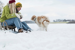 Couple sitting on a slide in snowy landscape and watching the dog shake the snow off his fur, Bavaria, Germany