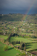 A rainbow descends on a cypress-lined winding lane and green farms below Orvieto, Umbria, Italy.
