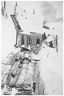"""RGS Goose #3 overturned at MP 52 on north side of Lizard Head Pass.  Henry Wolford is motorman and Forest Rassmussen is on work crew.  The Lorain shovel is the main actor in this play in deep snow.<br /> RGS  Lizard Head, CO  Taken by Wolford, Henry - ca. 1945<br /> In book """"Rio Grande Southern II, The: An Ultimate Pictorial Study"""" page 278<br /> Also in """"RGS Story Vol. X"""", p. 305.<br /> Same image as RDS059-014.<br /> Thanks to Don Bergman for additional information."""