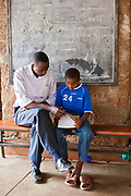 A young boy studies with his teacher at the AFCIC centre in Thika, Kenya. AFCIC - Action for children in conflict, help children who have been affected by various forms conflict or crisis.