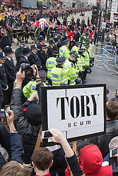 "© Licensed to London News Pictures . 17/04/2013 . London , UK . A protester holds up a "" Tory Scum "" placard as Baroness Thatcher's coffin passes at Ludgate Circus . The funeral of former British Conservative Prime Minister , Baroness Margaret Thatcher , today (Wednesday 17th April 2013) in Central London . Baroness Thatcher died from a stroke at the age of 87 . Photo credit : Joel Goodman/LNP"