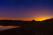 A man stands silhouetted against the vast expanse of sky where stars and the remnants of day meet within a drained Summersville Lake at dusk in West Virginia.