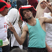 A drinks vendor shows off during the carnival atmosphere in Cairo's Tahrir Square.