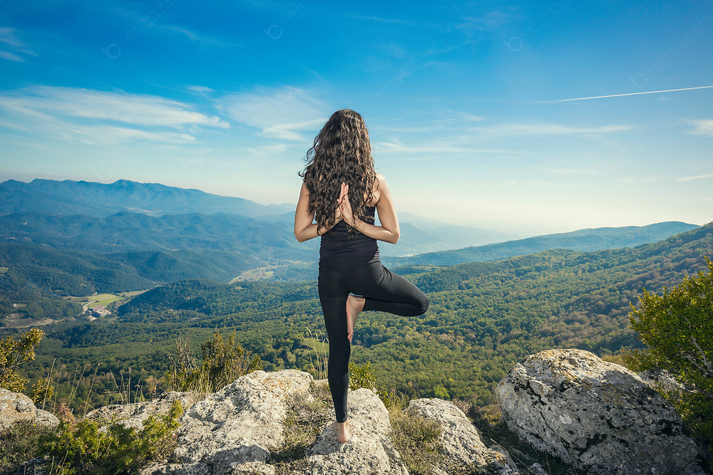 A young woman doing her yoga routines in nature Tree pose with reverse namaste
