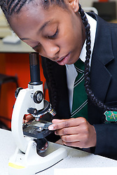 Secondary School student using a microscope to examine dust particles as part of the air quality unit of GCSE Science,
