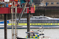 © Licensed to London News Pictures. 25/07/2020. London, UK. Three Extinction Rebellion activists have locked on to a drilling rig in the Thames close to the 02 Arena in Greenwich. The rig is involved with preparatory drilling for the Silvertown Tunnel which is planned to connect the Greenwich Peninsula with west Silvertown. Extinction Rebellion oppose the building of the tunnel due to the increase in air pollution it may cause. Photo credit: George Cracknell Wright/LNP