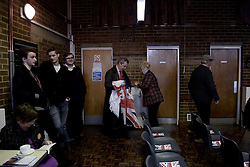 "© London News Pictures. ""Looking for Nigel"". A body of work by photographer Mary Turner, studying UKIP leader Nigel Farage and his followers throughout the 2015 election campaign. PICTURE SHOWS - Nigel Farage unfurls the flags of England and Great Britain at a public meeting in Cliffsend Village Hall, in Ramsgate, Kent, on March 31st 2015. The meeting was one of nearly thirty that Mr Farage spoke during his campain and was a key part of his election strategy. . Photo credit: Mary Turner/LNP **PLEASE CALL TO ARRANGE FEE** **More images available on request**"