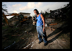 29 August 2006 - New Orleans - Louisiana. Lakeview. The one year anniversary of hurricane Katrina. Demolition man Jay Johnson of east Orleans stands in the rubble of what used to be an upscale upper middle class home he has just torn down. Johnson picked through the rubble for the copper piping to recycle. He was on speakerphone to the lead contractor who was moaning about his labor force and problems with crews, his 'boss' having just returned from yet another first class jet set holiday with all the cash he is now earning.