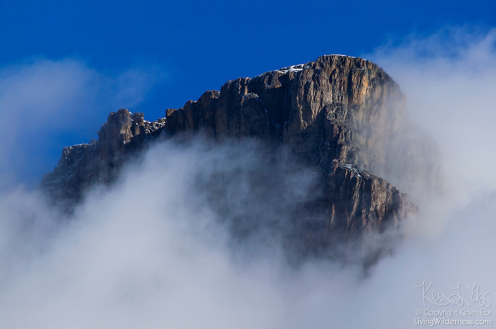 Low clouds and fog frame the summit of Castle Mountain, a 2,766 meter (9,075 foot) tall mountain located in Banff National Park, Alberta, Canada.