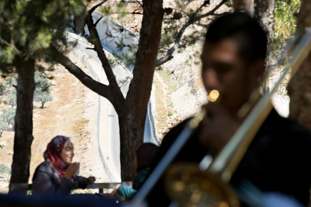 Members of Brass for Peace play in the grounds of Al-Quds University, occupied Palestinian territories. The group use music as a way of spreading messages of peace. The Separation Barrier can be seen in the background, dividing the town of Abu Dis