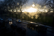 An aerial view of parked cars on a south London street, flooded by sunlight after heavy rainfall with out-of-focus spots of water on the glass of a residential houses window, on 25th February 2020, in London, England.