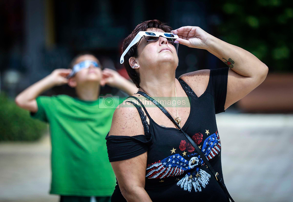 August 21, 2017 - Florida, U.S. - Ann Machado of West Palm Beach observes the eclipse at CityPlace in West Palm Beach Monday, August 21, 2017. ''It is amazing,'' she said. ''I am so glad I got the day off today. (Credit Image: © Bruce R. Bennett/The Palm Beach Post via ZUMA Wire)