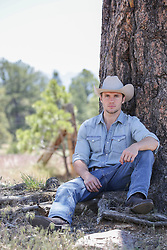 cowboy relaxing under a tree