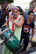 A band of Cubans play traditional music in the street, wearing costumes, drumming and dancing, Havana old town.