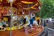 With many people and families staying in the UK for their Summer break during the school holidays, a large number of domestic tourists, who may normally have been travelling abroad, have decended on the capital to see the sights, as seen here with children and adults enjoying the merry-go-round carousel on the South Bank on 11th August 2021 in London, United Kingdom. Following the Coronavirus / Covid-19 health scare of the last two years, and with some travel restrictions still in place, more people have chosen a staycation which is a holiday spent in ones home country rather than abroad, or one spent at home and involving day trips to local attractions.