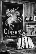 Waiter under old Cinzano sign wears Carlos Gardel tie, Ramos Generales cafe dates back to Salamon family 1906, Ushuaia, Argentina.