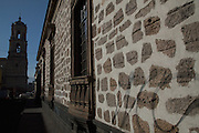 Wall on an ancient spanish style building in Morelia, Michoacan state Mexico with a view of the tower of Iglesia y Convento del San Francisco. The city is a UNESCO World Heritage Site and hosts on of the best preserved collection of Spanish Colonial architecture in the world.