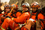 HEALDSBURG, CA - OCTOBER 26: A crew of inmate firefighters takes a break during firefighting operations to battle the Kincade Fire in Healdsburg, California on October 26, 2019.