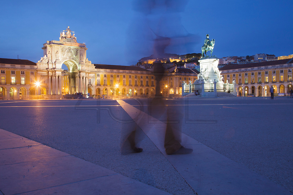 People passing by Terreiro do Paço, also know as Praça do Comércio (Commerce Square). This square is the largest in Lisbon and is located just by the river Tagus. From left to right can be seen Augusta Street Arch, the equestrian statue of King Joseph I and, on the top of the hill, Saint George Castle.
