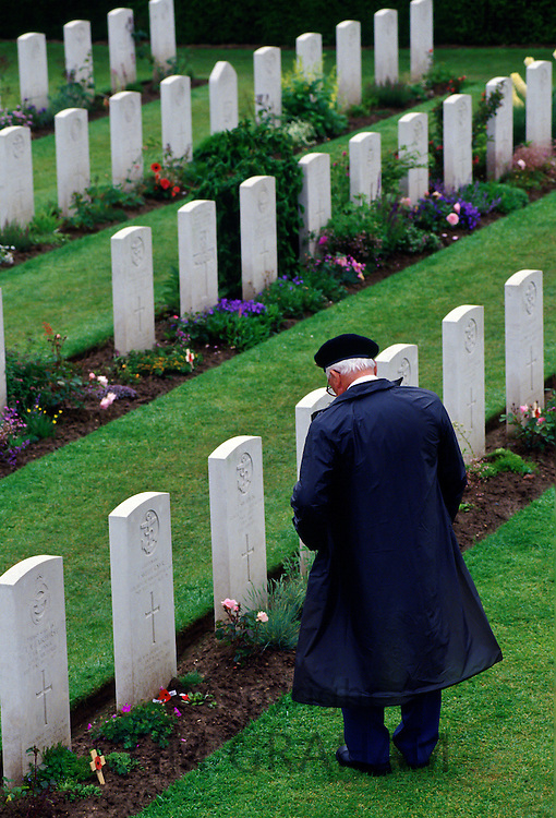 Veteran in military cap  looking at war graves in Commonwealth war cemetery, Normandy, France.