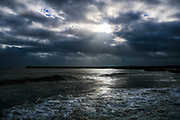 Sun breaks through dramatic clouds in the sky over Folkestone Harbour Arm during high tide from Sunny Sands Beach, Folkestone, Kent, UK. (photo by Andrew Aitchison / In pictures via Getty Images)