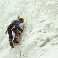 An ice climber ascends a frozen waterfall in Hyalite Canyon, near Bozeman, Montana.