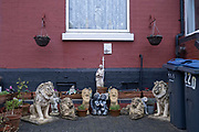 Small statue of Jesus looks down form a window above lions and other ornaments outside a home in Balsall Heath on 18th January 2020 in Birmingham, United Kingdom. Ornamental lions are often associated with stately homes, but here are outside inner city terraced houses.