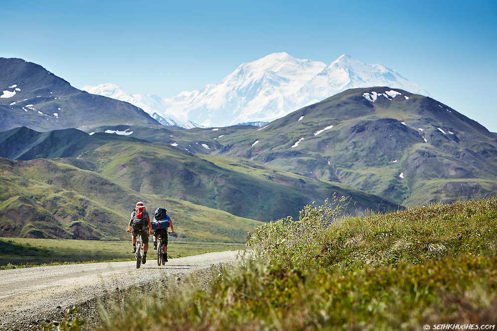 Two cyclists tour the Denali National Park road on bicycle with Mt. McKinley towering in the distance.