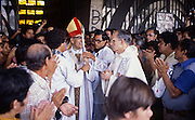 The martyr Archbishop Oscar Romero of El Salvador is greeted by clergy and several hundred of the faithful before a mass at Iglesia el Rosario -the Church of the Rosary - in San Salvador, El Salvador. The priest was later slain at the alter by a right wing gunman in 1980. Óscar Arnulfo Romero y Galdámez was a bishop of the Catholic Church in El Salvador. He became the fourth Archbishop of San Salvador, succeeding Luis Chávez, and spoke out against poverty, social injustice, assassinations and torture. Romero was assassinated while offering Mass on March 24,1980. To license this image, click on the shopping cart below -
