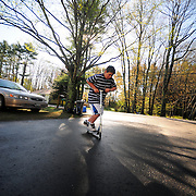May 8, 2009-- BRUNSWICK, Maine. Corey Taker, 10, drives his scooter into another trick at his bus stop in Brunswick on Friday morning. The sun held back predicted rain showers on Friday -- and most of the rest of the week has been the same. Photo by Roger S. Duncan.