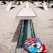 Flowers placed next to one of the benches of the Pentagon memorial. The Pentagon Memorial is in remembrance of the events of September 11, 2001, and the 184 people who died as victims of the terrorist attack on the Pentagon. The Memorial is adjacent to the southwest side of the Pentagon. Designed by Julie Beckman and Keith Kaseman, the memorial opened to the public on September 11, 2008, it is designed with one illuminated for each victim of the attack, arranged by the person's age. Each bench has a small pond of water underneath, and a name is etched on the end of each bench.