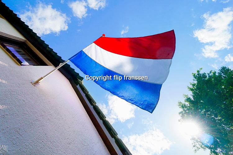 Nederland, Ubbergen, 5-5-2020 Aan de gevel van een huis hangt de nederlandse valg strak te wapperen tegen een blauwe lucht. Het is nationale bevrijdingsdag. Dit jaar een feest zonder evenementen vanwege de coronamaatregelen .FOTO: FLIP FRANSSEN