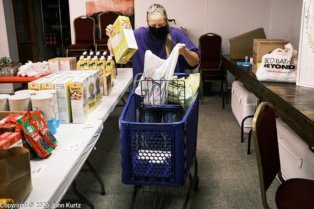 "16 SEPTEMBER 2020 - MITCHELLVILLE, IOWA: A woman picks up a box of cereal at the pantry in the Heritage Word of Life Church. There is no grocery store in Mitchellville, a small community in eastern Polk County. It doesn't qualify as a ""food desert"" under USDA guidelines because there are grocery stores within 10 miles in neighboring communities, but based on state data, Mitchellville is the poorest community in Polk County (which includes the Des Moines metropolitan area). The Mitchellville zip code has the lowest per capita income in Polk County. Many people don't own cars and can't get to neighboring communities to buy groceries. Every day someone from the Mitchellville library picks up hot meals from a nearby town and distributes them in the library. Heritage Word of Life, a church across the street from Library, has a food pantry in their Fellowship Room where people can pick up fresh vegetables, staples, and hygiene needs.        PHOTO BY JACK KURTZ"