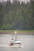 The view of a fishing boat from aboard the Alaska State Ferry Malaspina in the Wrangell Narrows, Southeast, Alaska.