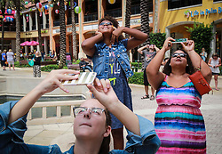 August 21, 2017 - Florida, U.S. - Angela (age 9, top center) watches the eclipse with mom Amber Kiringo of West Palm Beach and others at CityPlace in West Palm Beach Monday, August 21, 2017. ''It is pretty neat,'' said Amber. (Credit Image: © Bruce R. Bennett/The Palm Beach Post via ZUMA Wire)