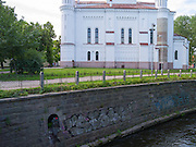 View of the mermaid in the wall along the Vilniau River, with graffiti; Vilnius, Lithuania