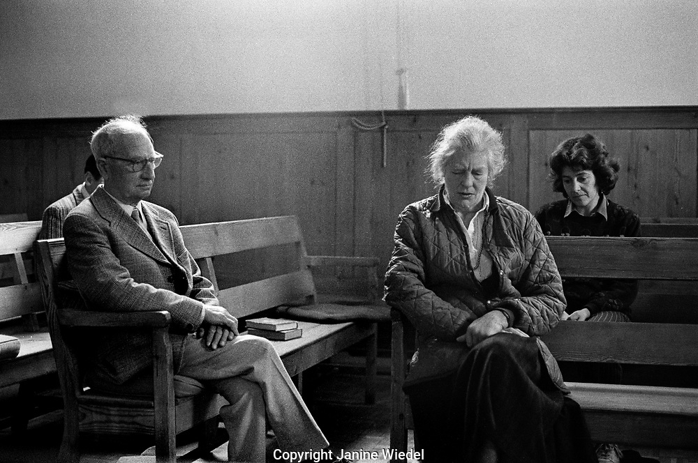 People sitting contemplating in  Silence in a Quaker Meeting House