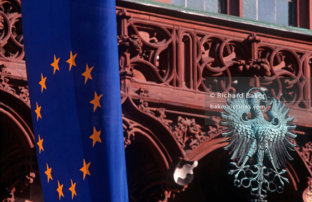 """An EU flag and the Prussian Eagle sit side-by-side, on 16th May 2000, in Frankfurt, Germany. The EU flag hangs limply alongside the old German world Prussian eagle near the balcony of Frankfurt's Rathaus or Town hall in historic Romerberg Square. The yellow stars formed into a circle of the European Union member states lie on a background of blue but the bronze green eagle harks back to a previous era of German politics and culture. The state of Prussia developed from the State of the Teutonic Order. The original flag of the Teutonic Knights had been a black cross on a white flag. Emperor Frederick II in 1229 granted them the right to use the black Eagle of the Holy Roman Empire.[citation needed] This """"Prussian Eagle"""" remained the coats of arms of the successive Prussian states until 1947. (Photo by Richard Baker / In Pictures via Getty Images)"""