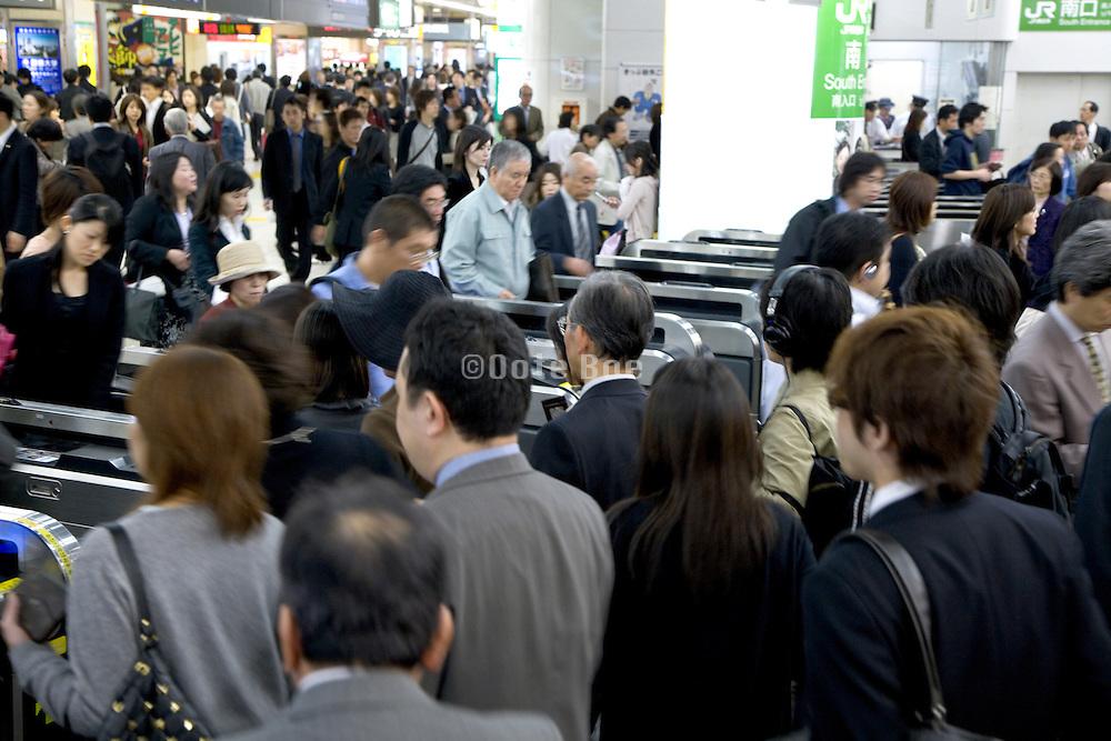 daily business commuters going through the turnstile at the Shinjuku railway station Japan