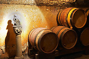 Wooden barrels with aging wine in the cellar of Guigal in Ampuis. A statue on a piedestal in the underground cellar at Guigal showing a small bacchus sitting on a wine barrel holding a grape bunch in his hand.  Domaine E Guigal, Ampuis, Cote Rotie, Rhone, France, Europe