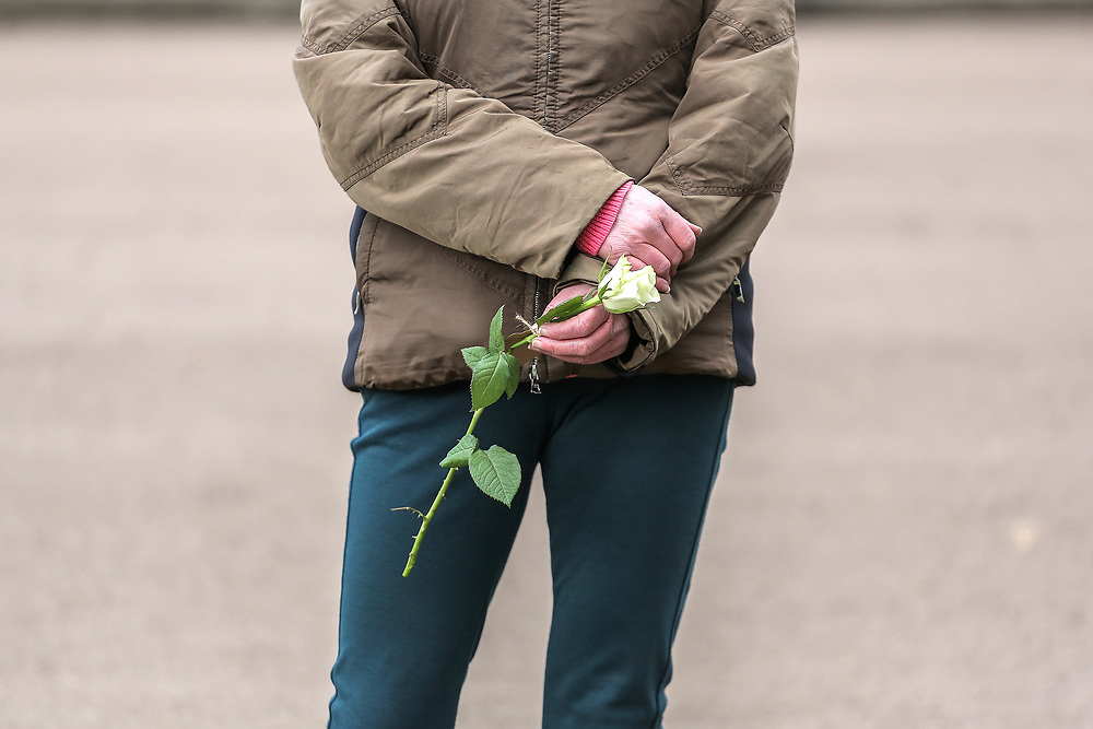 13th, March, 2021. Cheltenham, England. A member of the public holds a single flower in memory of Sarah Everard.
