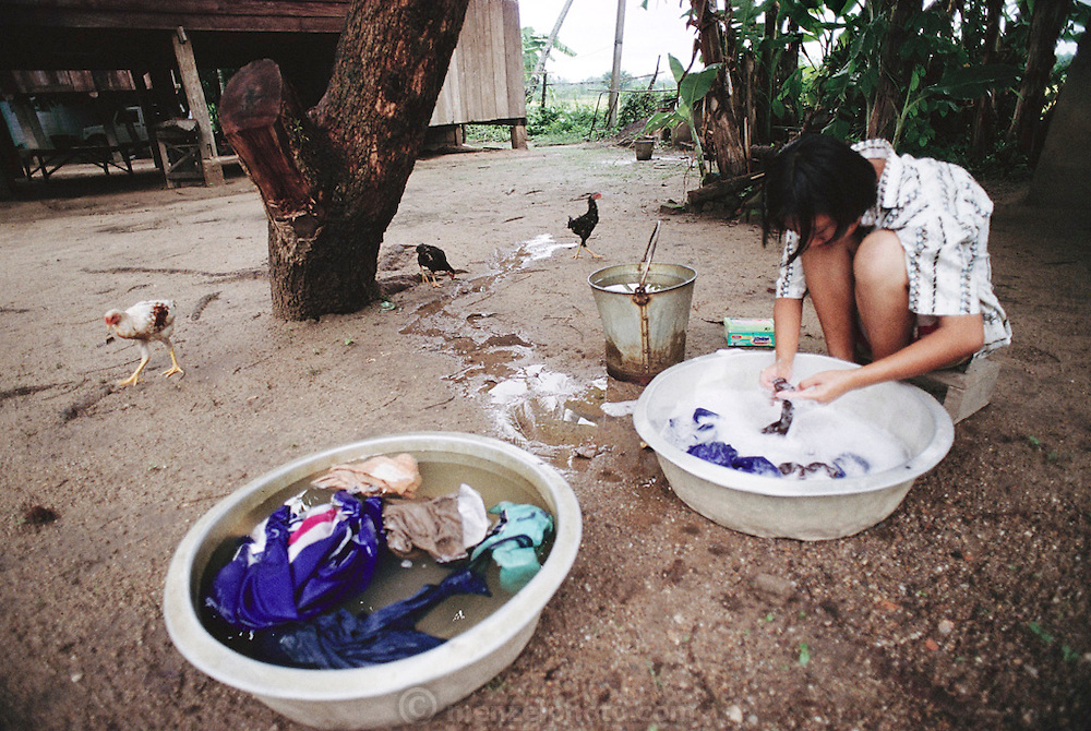 Buaphet Khuenkaew washes her family's clothes on the ground near her house. She and her family live in the wooden 728-square-foot house on stilts, surrounded by rice fields in the Ban Muang Wa village, outside the northern town of Chiang Mai, in Thailand. Material World Project.