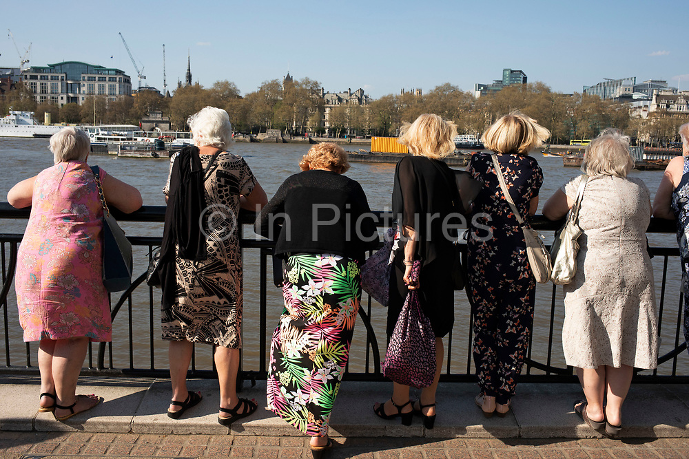 Group of middle aged and elderly ladies wearing their best dresses lined up to look out at the River Thames along the South Bank in London, England, United Kingdom. The South Bank is a significant arts and entertainment district, and home to an endless list of activities for Londoners, visitors and tourists alike.
