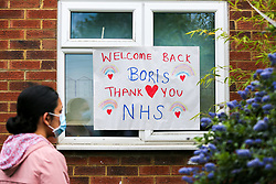 © Licensed to London News Pictures. 27/04/2020. London, UK. A woman wearing a face mask looks at a 'Welcome Back Boris. Thank you NHS' sign displayed in a window in a house in north London. British Prime Minister Boris Johnson returns back to work after recovering from COVID-19. Photo credit: Dinendra Haria/LNP