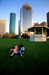 Stock photo of a man and two women relaxing on the grass in Sam Houston Park in downtown Houston Texas