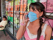 Apr. 27, 2009 -- NOGALES, SONORA, MEXICO: Erika Medina uses her cell phone to call a friend after buying a surgical mask to protect herself from the swine flu in Nogales, Sonora, Mexico. The Mexican government broadened its efforts to control the outbreak of swine flu Monday closing schools throughout the country. In Nogales, on Mexico's northern border with the US, people started wearing masks as news of the outbreak spread.  Photo by Jack Kurtz