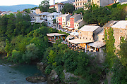 The busy old market bazaar street Kujundziluk with lots of tourist craft and art shops and street merchants. Restaurants cafes along the river. Seen from the old bridge. Historic town of Mostar. Federation Bosne i Hercegovine. Bosnia Herzegovina, Europe.