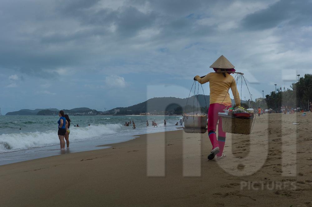 A Vietnamese woman carries a yoke on her shoulder along a Nha Trang beach, Vietnam, Southeast Asia
