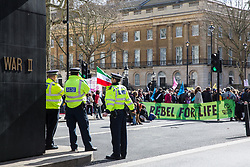 London, UK. 9th March, 2019. Climate activists from Extinction Rebellion block Whitehall after pouring artificial blood on the ground outside Downing Street as part of an act of civil disobedience named 'The Blood of Our Children' to call on the Government to take immediate steps to combat the current climate and ecological emergency.